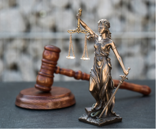 Wooden gavel with a metal lady justice statute on a table.