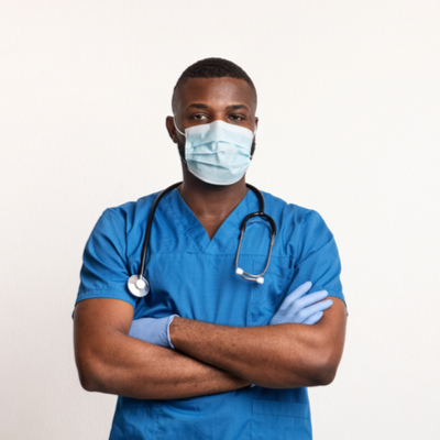 Male black medical professional in scrubs and mask with arms crossed