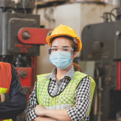 Female worker in a manufacturing site wearing a mask and hard hat