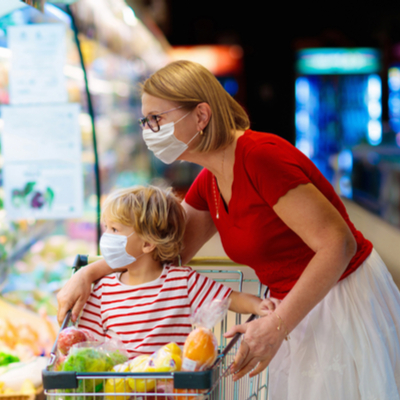 Woman and child shopping at grocery store in masks